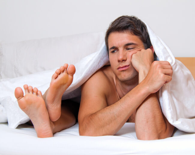 Man in bed next to feet