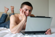 Shirtless man with a computer