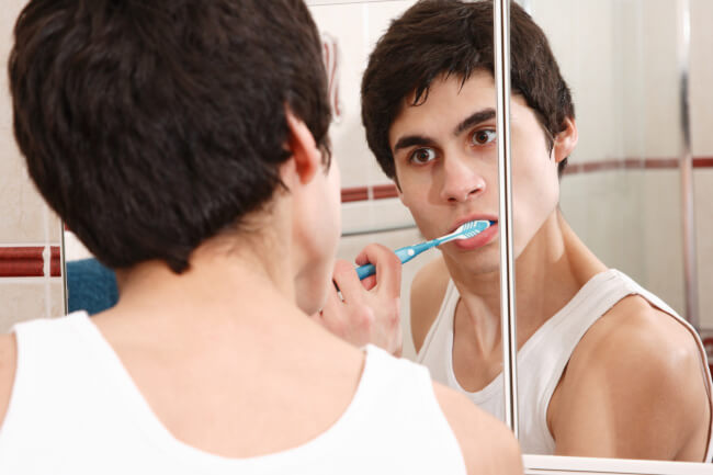 Young man brushing his teeth - deposit