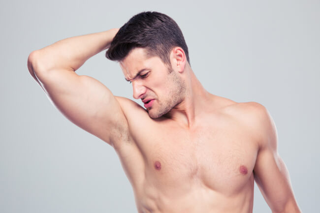 Young man sniffing his armpit - deposit
