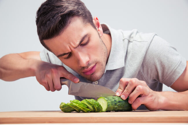 Man cutting cucumber
