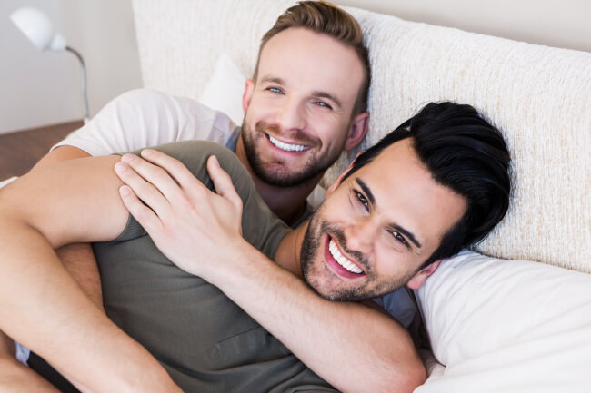 Happy gay couple in bed