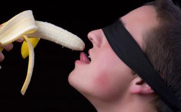 Man eating a banana blindfolded