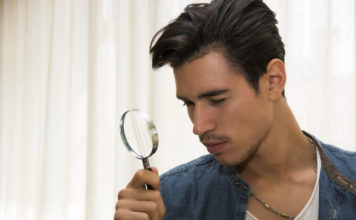 Man holding magnifiying glass
