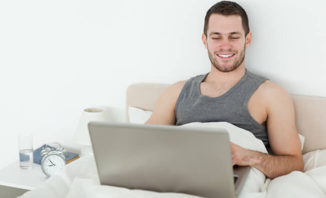 Man in bed with a laptop