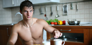 Shirtless man sitting in the kitchen