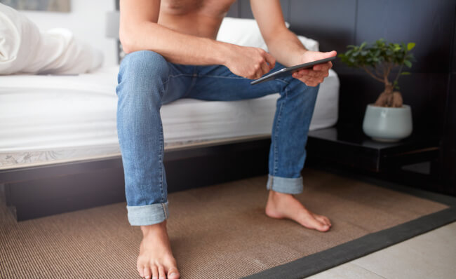 Man holding tablet in bed