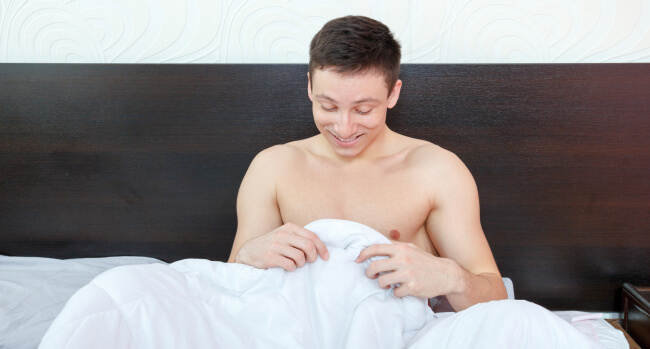 Man in bed looking doing smiling