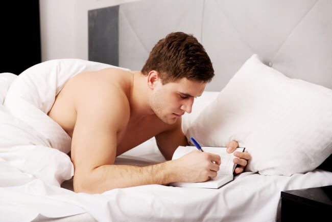 Man writing in notebook in bed