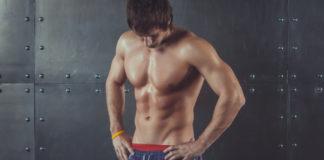 Muscular shirtless man looking down