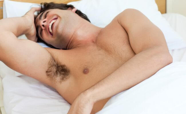 Man laughing in bed