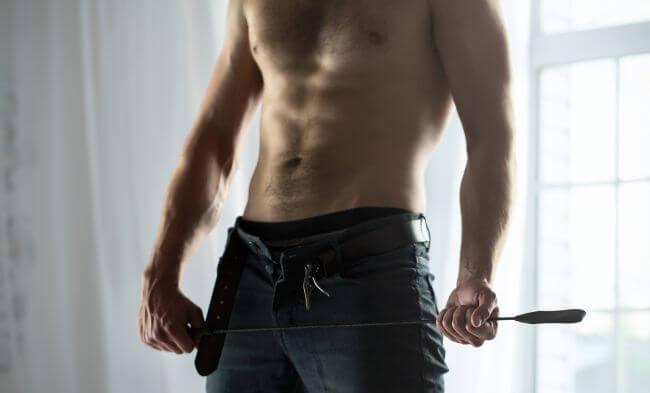 Man shirtless with whip BDSM