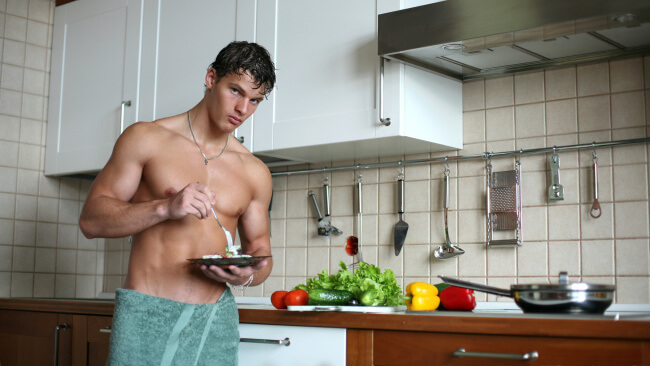Shirtless man eating breakfast in the kitchen