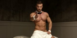 Shirtless man in hotel bed