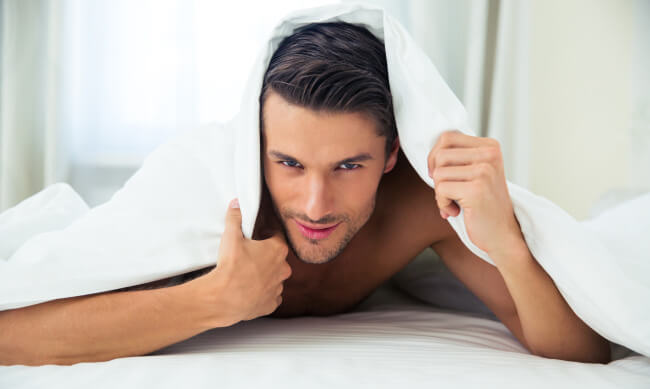 Man in bed under a blanket