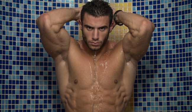 Shirtless man taking a shower