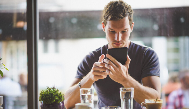 man with tablet in coffee shop