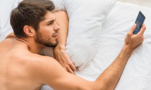 Man in bed with a phone