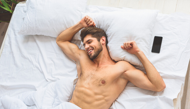 Shirtless guy in bed happy