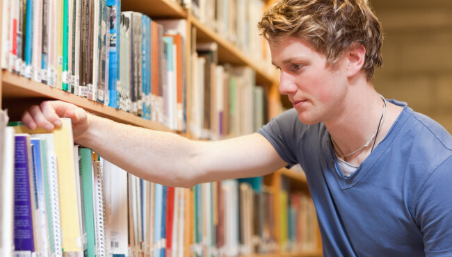 student in the library with books and magazines