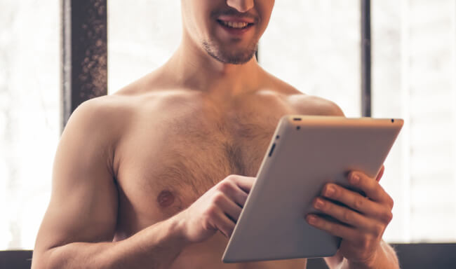 Shirtless man with tablet