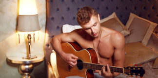 Shirtless man playing guitar