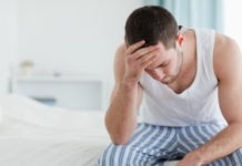 Man in pain sitting on bed