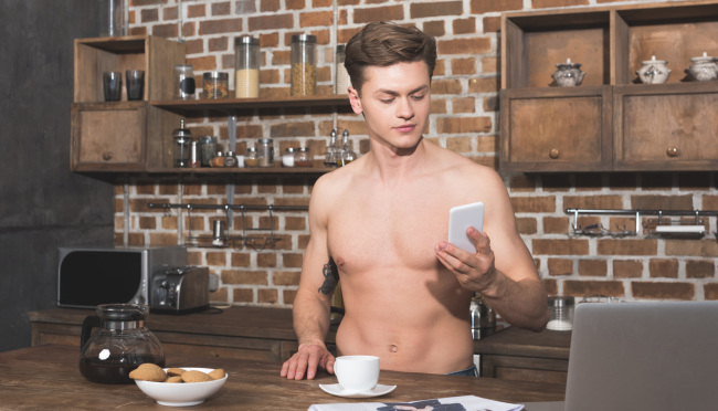 Shirtless man holding phone
