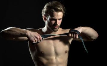 Shirtless man holding a belt spanking