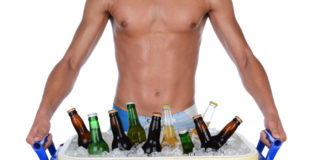 Shirtless man carrying beer