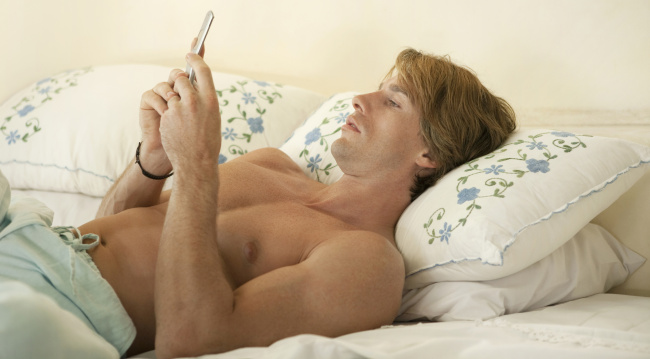 Man shirtless in bed with phone
