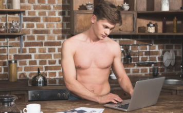 Shirtless man using computer laptop